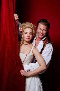 Emanuel und Elenore stehen hinter einem Vorhang