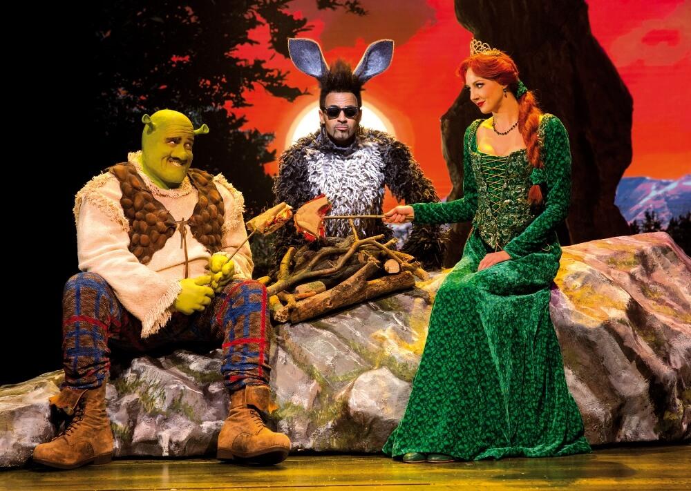 Shrek, der Esel und Prinzessin Fiona sitzen am Lagerfeuer.